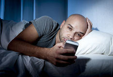 Young cell phone addict man awake at night in bed using smartphone Stock Image