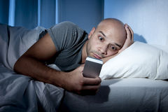 Young cell phone addict man awake at night in bed using smartphone Stock Photo