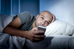 Young cell phone addict man awake at night in bed using smartphone Royalty Free Stock Photography