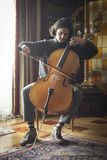 Young cellist playing cello seriously. Full body shot of a young cellist with long hair and moustache playing cello on an elegant house environment Royalty Free Stock Photography