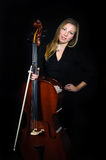Young cellist standing on black background. And smileing stock images