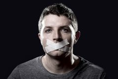 Young censored man mouth sealed on tape to prevent free speaking Royalty Free Stock Image