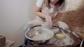 Young ceramist woman is working alone in pottery shop with potter`s wheel. Female sculptor is making ceramic cup using potter`s wheel in workshop. She is sitting stock footage
