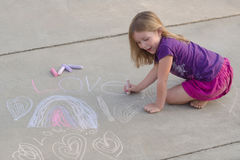 Young Chalk Artist. A six year old girl creates her designs on a sidewalk with chalk Royalty Free Stock Images