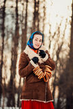 Young  charismatic attractive  woman clothed sheepskin coat and scarf. Girl holding the bagels. Spring time Stock Photos