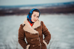 Young  charismatic attractive  woman clothed sheepskin coat and scarf. Girl looks at camera near big river. Spring time Royalty Free Stock Photography