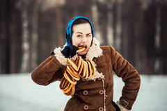 Young  charismatic attractive  woman clothed sheepskin coat and scarf. Girlthe bites off the bagel. Spring time Stock Images