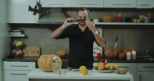 Young charismatic man playing with knife in the kitchen prepare for Halloween party, beautiful Halloween decorations. stock video footage