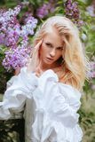 Portrait of a girl blondes with lilac bush. stock photos