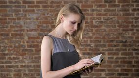 Young charming blond girl is reading book, watching at camera, brick background.  stock footage