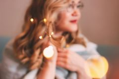 Young charming blonde woman in glasses with lights in her hair, romantic atmospheric photo about dreams, blurred focus. The Young charming blonde woman in stock images
