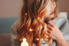 Young charming blonde woman in glasses with lights in her hair, romantic atmospheric photo about dreams. The Young charming blonde woman in glasses with lights royalty free stock images