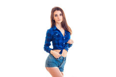 Young charming brunette with beautiful hair and a blue shirt with shorts keeps her hands in her pockets and looks into Royalty Free Stock Images