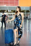 Young charming brunette. Posing at the airport standing next to a suitcase dressed in a long dress stock photo