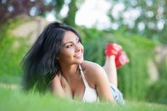 Young charming brunette. Posing outdoors lying on the green grass royalty free stock photos