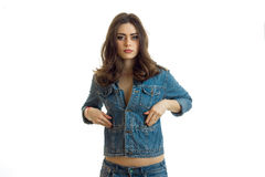 Young charming brunette stands upright in a jeans jacket and looks into a camera. Isolated on white background Stock Images