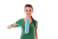 Young charming brunette woman in uniform makes renovation with paint roller in her hands smiling on camera isolated on Royalty Free Stock Photo