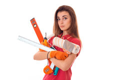 Young charming builder girl in uniform with a lot of tools makes renovation isolated on white background Royalty Free Stock Photo