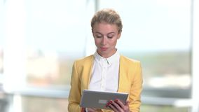 Young charming business lady using digital tablet. Gorgeous business woman working on pc tablet on blurred background. People, business and modern technology stock footage