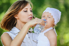 Young charming caring mother gives daughter drink Stock Photo