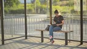 Young charming Caucasian female with trendy look use tablet while waiting transport on bus stop, woman sitting on a stock footage