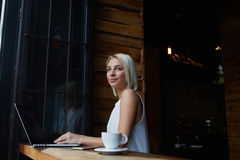 Young charming European woman dreaming about something while sitting with laptop computer in modern coffee shop,. Thoughtful attractive female freelancer using Royalty Free Stock Image