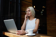 Young charming female freelancer calling with mobile phone while sitting in cafe at the table with net-book, Stock Photography