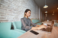 Young charming female freelancer thinking about new ideas during work on laptop computer. Beautiful woman dreaming about something while sitting with portable Royalty Free Stock Photos