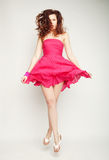 Young charming female in pink dress jumping Stock Photos