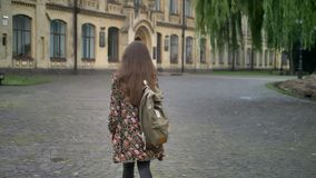 Young charming female student with long hair turning around and going to university, walking in park near college