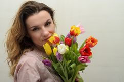 Young charming girl with a bouquet of flowers - multi-colored tulips stock photography
