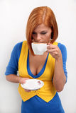 Young charming girl in bright clothes with a cup. Portrait of young charming girl in bright clothes with a cup of coffee on a white background Royalty Free Stock Image