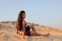 Young charming girl in desert. The charming young girl sits on a sandy dune Royalty Free Stock Photography