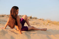 Young charming girl in desert. The charming young girl with long hair on a sandy dune Stock Photography