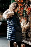 Young charming girl in a down jacket with a fur collar posing in a park on a sunny day royalty free stock images