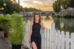 Young charming girl in a dress during a walk at sunset along the Tiber River embankment near the Vatican.  stock image