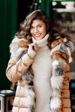 Young charming girl dressed in beige knit dress and a light brown down jacket with fur poses in the street royalty free stock photo