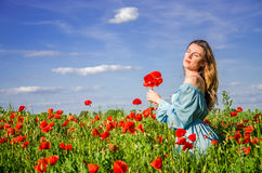 A young charming girl with long hair walks on a bright sunny summer day in a poppy field and makes a bouquet of poppy flowers Royalty Free Stock Photo