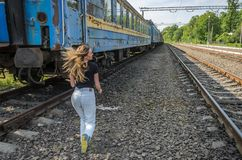 A young charming girl runs after the old railway carriage of a departing train.  Stock Photos