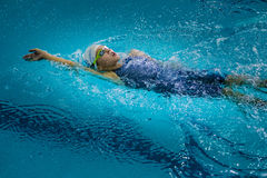 Young charming girl swims backstroke. Chelyabinsk, Russia - October 21, 2015: young charming girl swims backstroke during Championship of Chelyabinsk swimming Royalty Free Stock Images