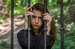 Young charming girl the teenager with long hair sitting behind bars in prison prisoner in a medieval jail with sad, pleading eyes Royalty Free Stock Photo
