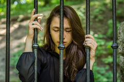 Young charming girl the teenager with long hair sitting behind bars in prison prisoner in a medieval jail with sad, pleading eyes. Of mercy Royalty Free Stock Photo