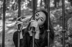 Young charming girl the teenager with long hair sitting behind bars in prison prisoner in a medieval jail with sad, pleading eyes Royalty Free Stock Photography