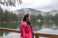 Young charming girl tourist stands on the shores of Synevyr lake among the mountains royalty free stock photo