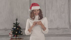 Young charming girl using internet on her phone. Young smiling woman doing online shopping before christmas. Professional shot on BMCC RAW with high dynamic stock video footage