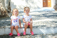 Young charming girls sitting at street in old Royalty Free Stock Images