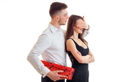Young charming guy brought a girl gift and closed her eyes hand Royalty Free Stock Images