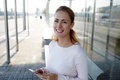 Young charming hipster girl with cute smile holding smart phone and smile to the camera while waiting a bus on station Royalty Free Stock Photography