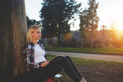 Young charming hipster girl dreaming about something while sitting with portable touch pad in park in spring evening, Royalty Free Stock Images