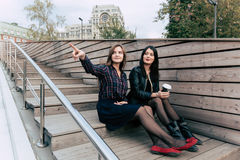young charming hipster girls look at the landscape of the city while relaxing after strolling outside in weekend Stock Photography